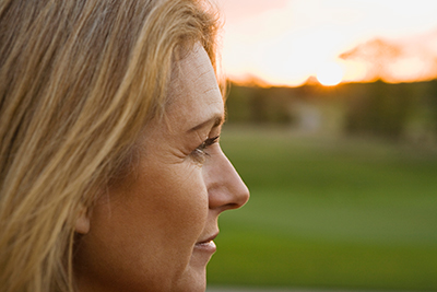 Distant Caregivers Image - Woman looking in distance, thinking of aging mother